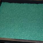 Резиновая зеленая крошка в лотке для холодного прессования