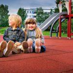 Дети на игровой площадке с резиновой плиткой
