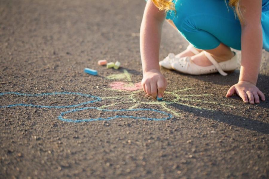 Девочка рисует на асфальте