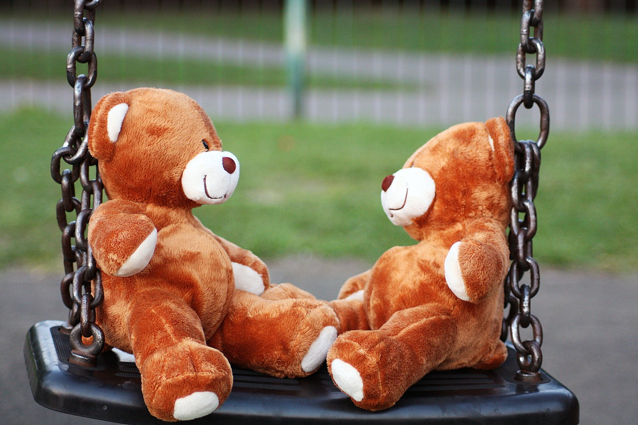 Мишки Тедди на качелях детской площадки