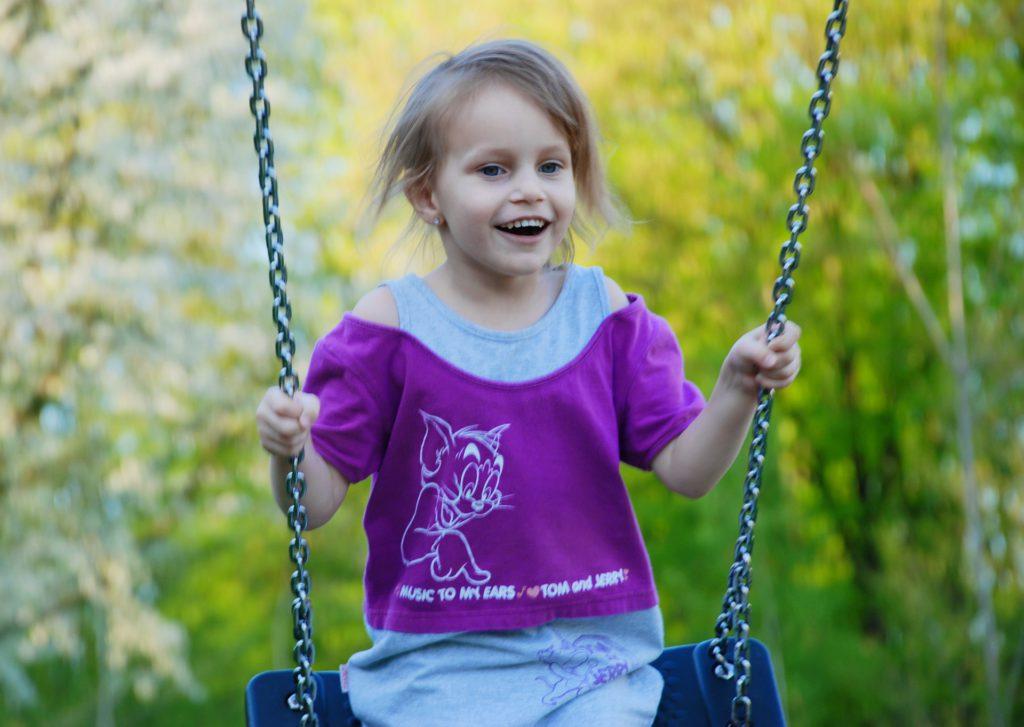 Счастливый ребенок качается на качелях