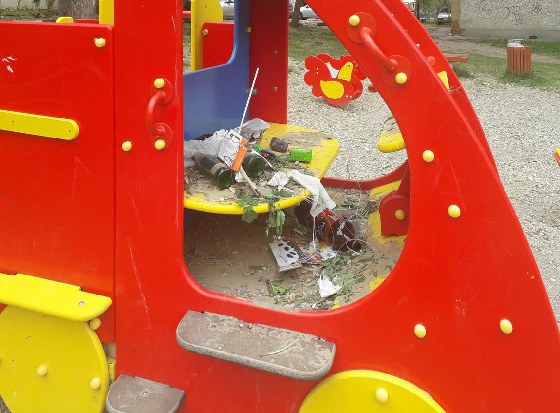 Бутылки и грязь на детской площадке