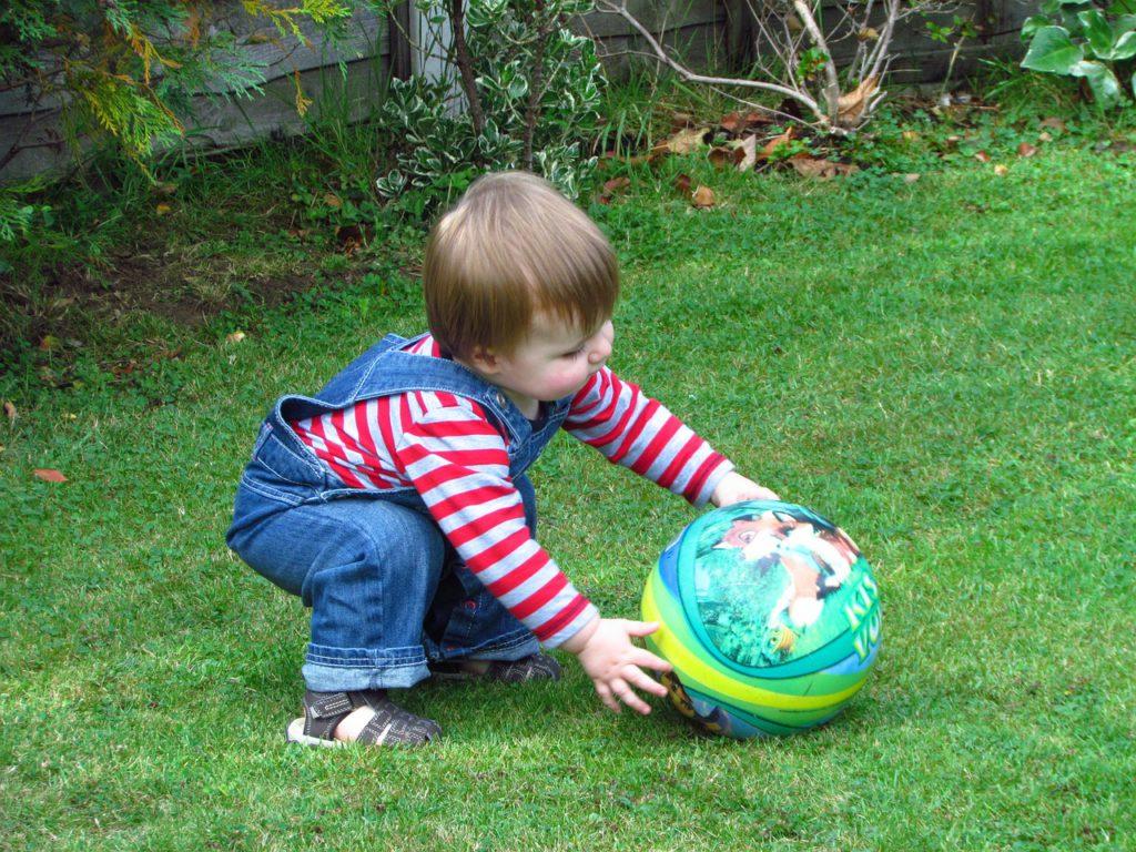 Ребенок играет с мячиком на траве