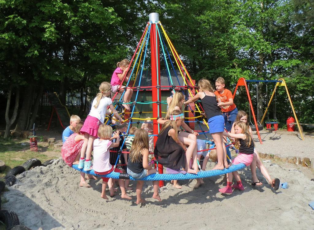 Дети на детской площадке с песчаным покрытием