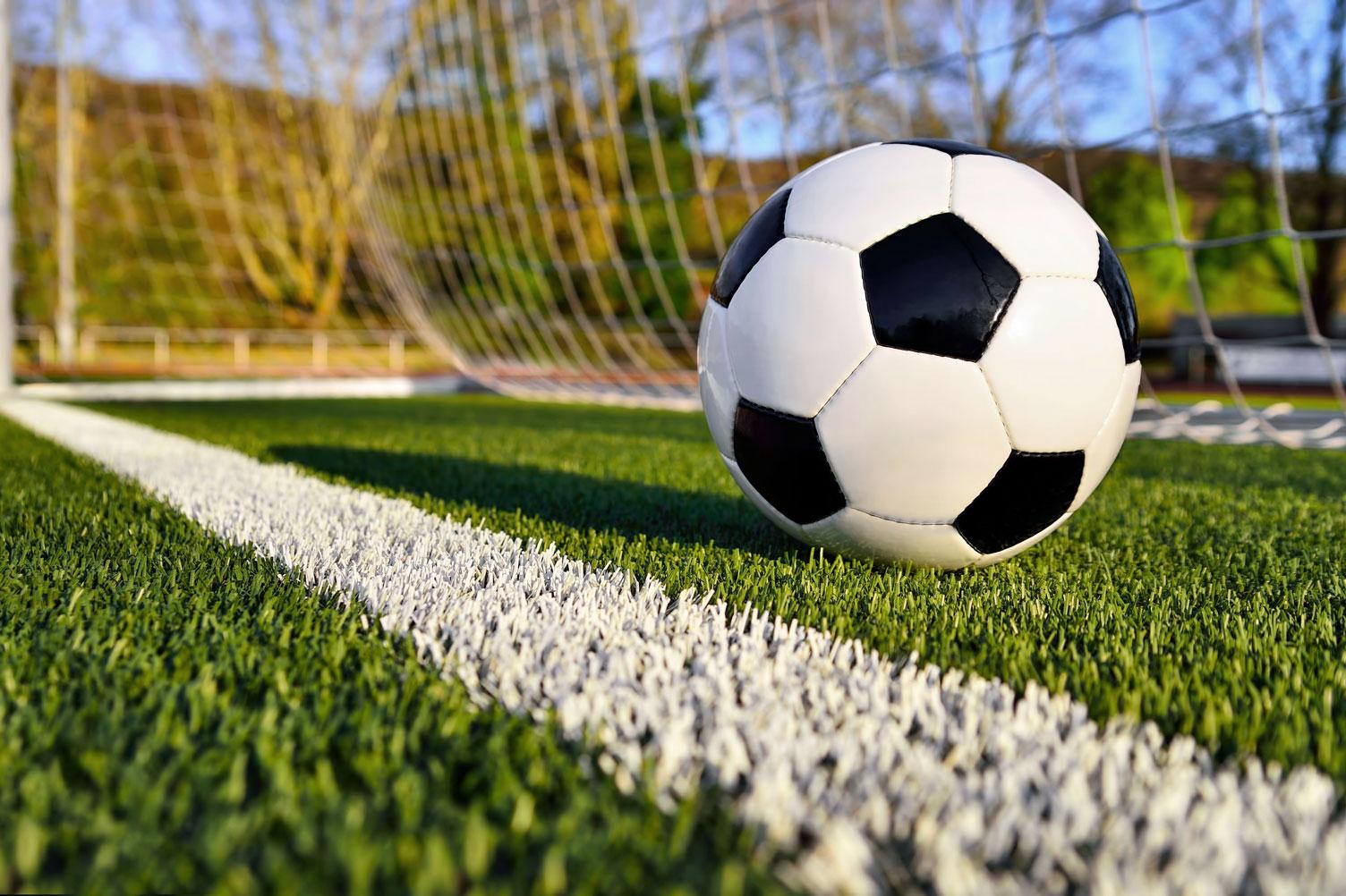 Мяч на зеленом футбольном поле